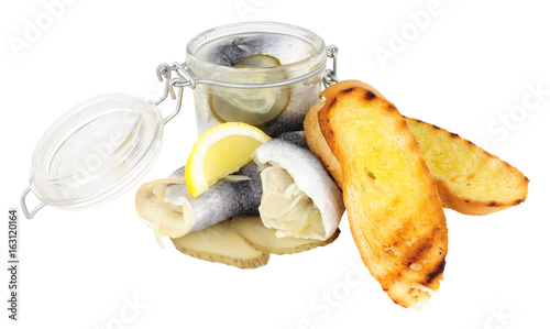 Vászonkép Pickled rollmop herrings in a glass storage jar and toasted bread isolated on a