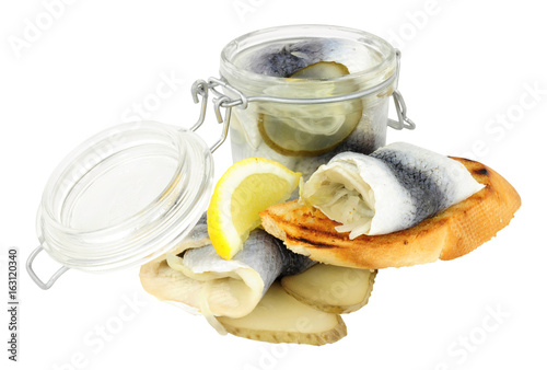 Fotografie, Obraz  Pickled rollmop herrings in a glass storage jar and toasted bread isolated on a