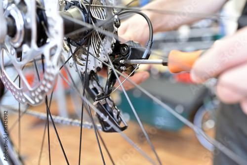 Zdjęcie XXL Obwód na rowerze przez mechanika w warsztacie rowerowym // Obwód na rowerze przez mechanika w warsztacie rowerowym