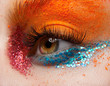 Macro and close-up creative make-up theme: Beautiful female eye with red and blue sparkles and orange pigment