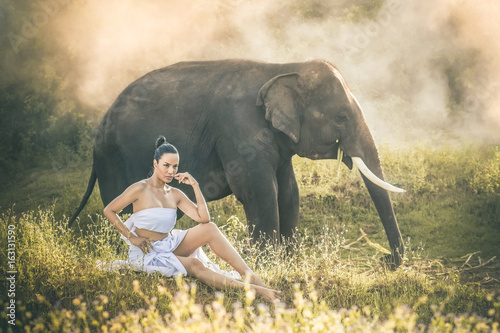 Photo Women wearing white clothes and the elephants in the forest.