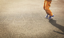 Little Boy Playing Hopscotch On Playground