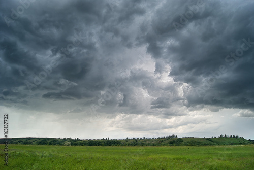 Storm cyclone over summer fields, hills and forests Fototapete