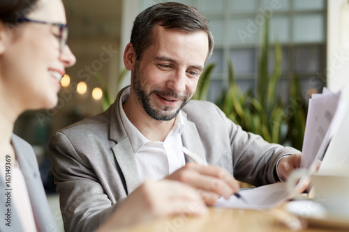 Fototapeta Happy man signing business document after negotiating obraz