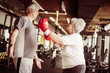 Senior couple boxing together in the gym. Senior woman with boxing glove.