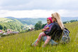 Happy mother with a child sitting on the grass on a background of forested mountains