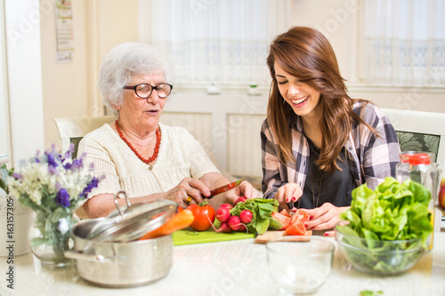 Photo sur Aluminium Cuisine Grandmother and granddaughter preparing food at home.
