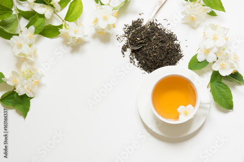 Poster Muguet de mai Jasmine dry green tea leaves with jasmine flowers and cup of tea on white background. Copy space and top view. Teatime.