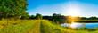 Sommerliche Landschaft mit Fluss bei Sonnenuntergang