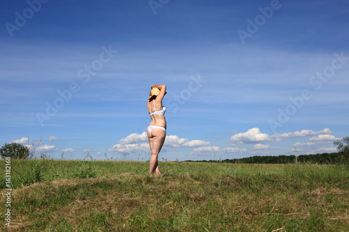Kobieta w bieliźnie z boku na tle nieba i łąki.