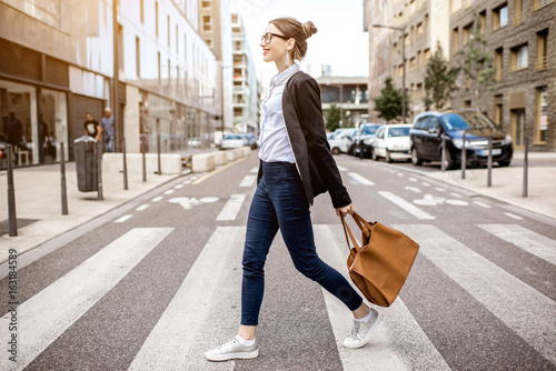 obraz PCV Young businesswoman crossing the street at the modern office district in Lyon city