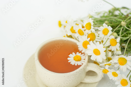 Poster Muguet de mai cup of herbal chamomile tea with fresh daisy flowers. doctor treatment and prevention of immune concept, medicine - folk, alternative, complementary, traditional medicine