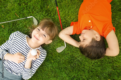Poster Golf Cute children with ball and drivers lying on golf course
