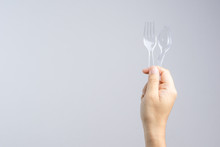 Hand Holding Plastic Spoon And Fork