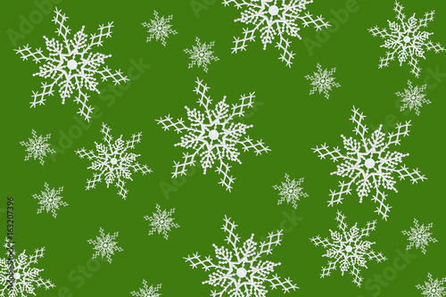 White plastic snowflake ornaments on green background