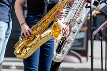 Quartet Of Young Saxophonists Playing Saxes During Street Performance