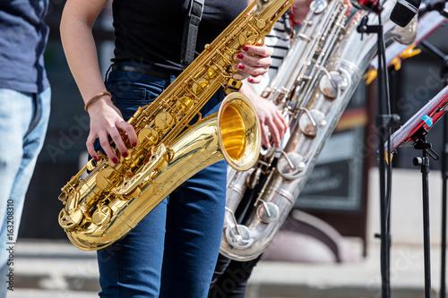 Zdjęcie XXL kwartet młodych saksofonistów grających saksami podczas występów ulicznych