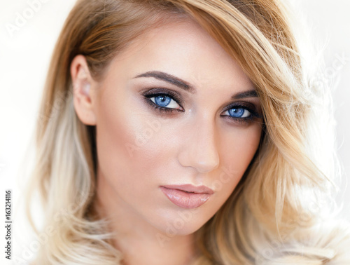 Portrait of a beautiful young blonde girl close-up. The model looks into the camera. Natural blue eyes