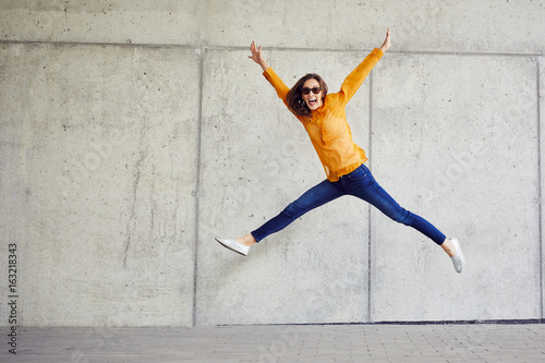 Ecstatic young woman jumping in joy and raising arms in urban outside setting Wallpaper Mural