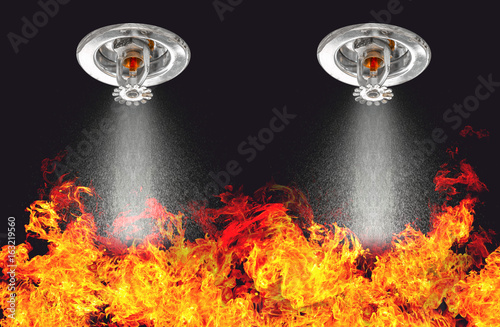 Obraz Image of Fire Sprinklers Spraying with fire background. Fire sprinklers are part of an overall safety protocol for fire and life safety. - fototapety do salonu