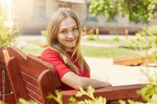 Valokuva  Sideways portrait of beautiful female with blonde hair, smiling into camera havi