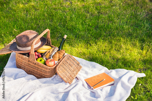 Stickers pour portes Pique-nique Close-up view of picnic basket with fruits and wine, hat and notebook with pencil on grass