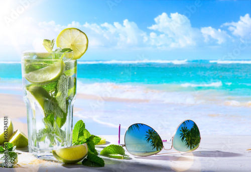 tropic summer vacation; Exotic drinks on blur tropical beach background