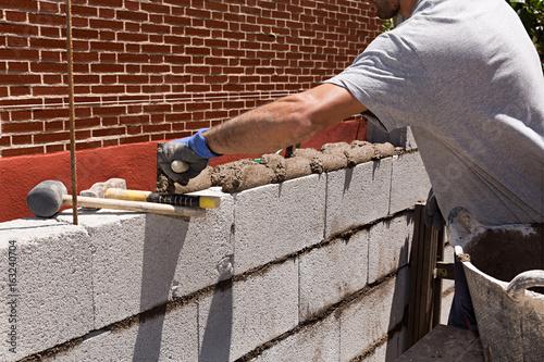 Foto op Plexiglas Wand Obrero construyendo un muro de bloques de hormigón 1.