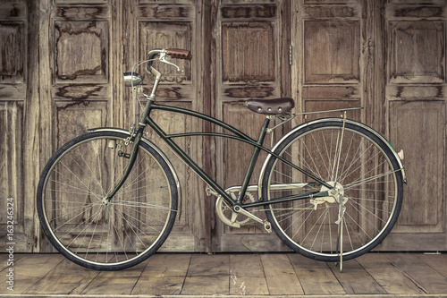 In de dag Fiets vintage bicycle on vintage wooden house. vintage tone. Thai style vintage wooden door not Wood stain. the door made of Teak wood (Tectona grandis) is Auspicious Tree in Thailand