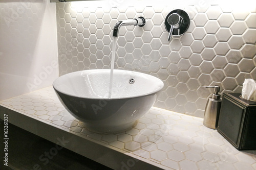 Modern wash basin with running water from tap faucet