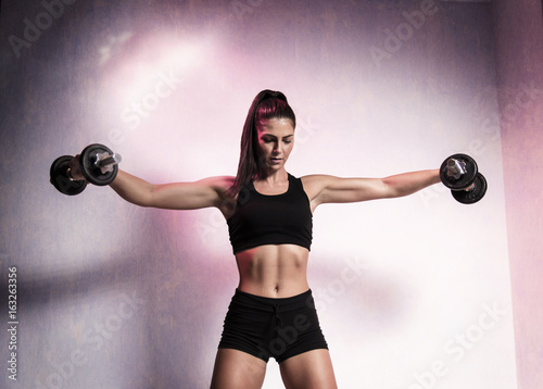 Fotografia  Attractive muscular young woman doing shoulder exercise with dumbbells