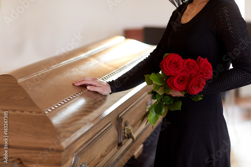 Photo woman with red roses and coffin at funeral