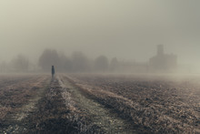 Unidentifiable Woman In The Distance Looking At A Church In The Dense Fog Of The Lombardy Region Of Italy During The Winter, Frozen Corn Field