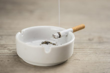 Lit Cigarette Burning In Ashtr...