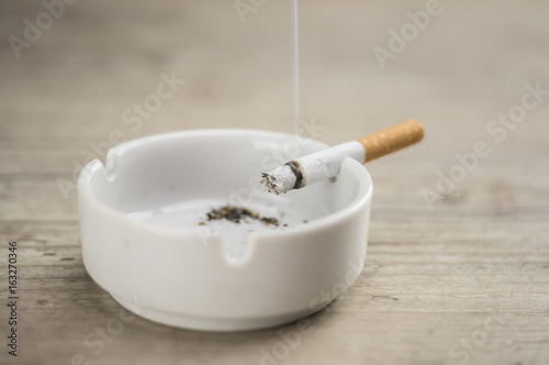 Lit cigarette burning in ashtray close up Canvas Print