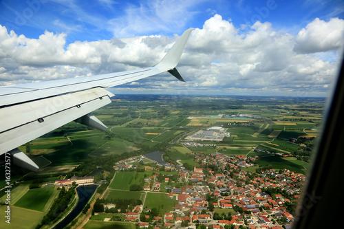 Widok miasta i pól z okna lecącego samolotu. - 163273577