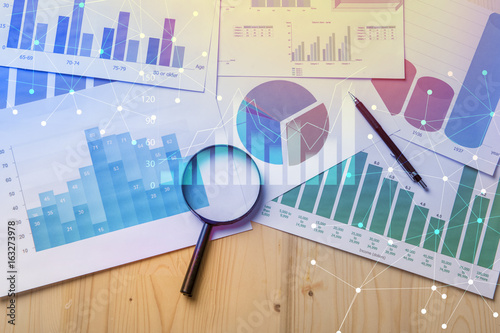 Leinwand Poster Magnifying glass and documents with analytics data lying on table,selective focu