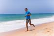 Man running on sunny beach near ocean