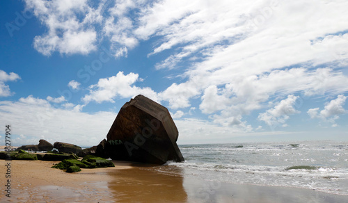 Blockhouse on the beach with blue sky and clouds Canvas Print