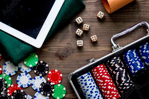Pocker set in a metallic case nearby tablet on a wooden table top view плакат