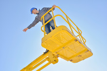Man In Cherry Picker Bucket Pointing Into Distance