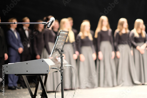 Photographie Microphone and music stand in front of electric pianos on the stage of the theat