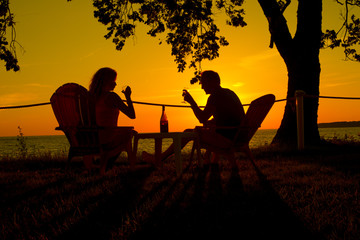 Fototapeta na wymiar couple drinking wine against sunset as silhouette