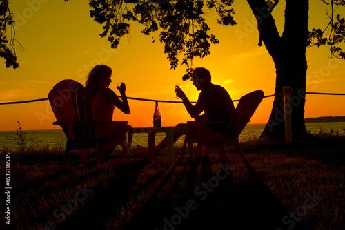 Obrazy na płótnie Canvas couple drinking wine against sunset as silhouette