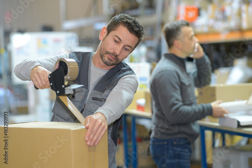 Obraz man working at warehouse while manager on the phone - fototapety do salonu