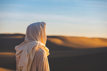 Jesus Christ Looks Out At A Setting Sun In The Sand Dunes.