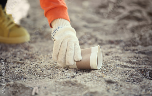 Photographie  Volunteer picking up litter from sand, closeup