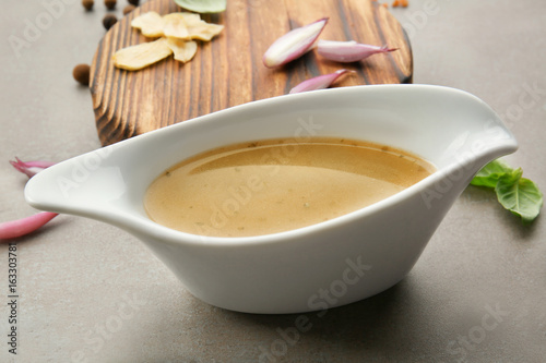 Sauce boat with turkey gravy and spices on table