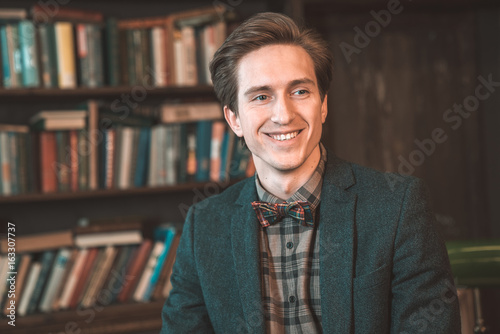 Fototapety, obrazy: Portrait of a smiling man in a library
