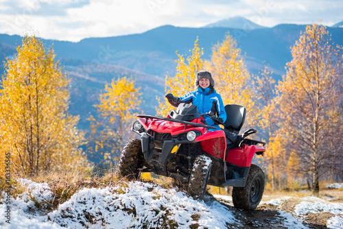 Smiling woman in blue jacket riding a red quadbike on snow-covered hill at sunny day against trees with yellow leaves and mountains. Blurred background